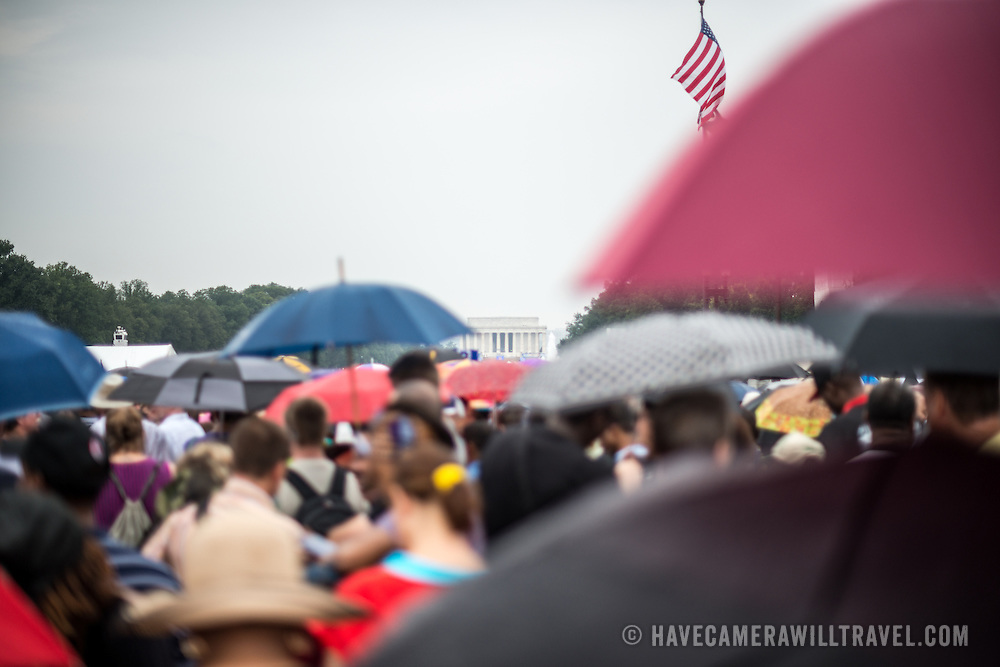 """People shield themselves from the light rain with umbrellas on Washington DC's National Mall at the commemoration of the 50th anniversary of the 1963 March on Washington famously remembered for civil right leader Martin Luther King Jr's """"I Have a Dream"""" speech."""