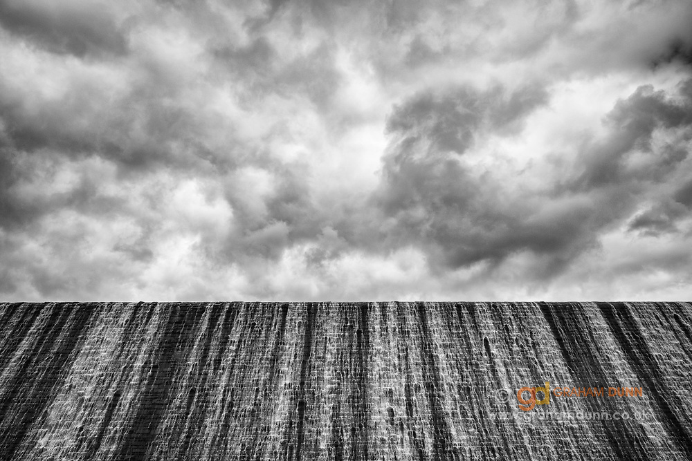 High waters in Derwent Reservoir flow dramatically over Derwent Dam below stormy skies. Derbyshire, Peak District, UK.