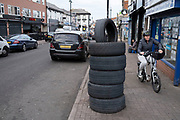 Woman cycling past a pile of tyres on the pavement outside a garage on Ladypool Road while the second national lockdown continues in Sparkhill as all non-essential shops are closed on 24th November 2020 in Birmingham, United Kingdom. The national lockdown is a huge blow to the economy and for individual businesses who were already struggling with only offering limited services.