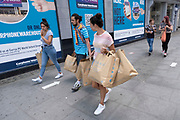 As some non-essential shops re-open, shoppers return to Oxford Street with numerous Primark shopping bags, while social distancing measures are put in place by the various retail shops which are open on 26th June 2020 in London, England, United Kingdom. As the July deadline approaces and government will relax its lockdown rules further, the West End remains quiet, apart from this popular shopping district, which itself has far fewer people on its pavements than normal.