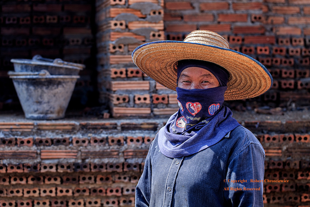 Masked Smile: A woman construction worker is completely covered in heavy clothing and hat that protect her from the blazing tropical sun, near Pai Thailand.