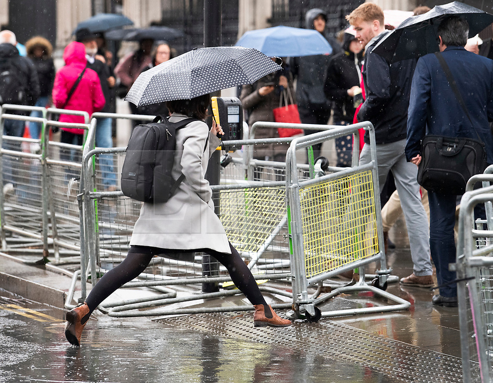 © Licensed to London News Pictures. 08/05/2019. London, UK. A woman leaps over a puddle in Westminster in London as wet and windy weather hits the capital. Heavy rain is forecast for most of the UK this week. Photo credit: Ben Cawthra/LNP
