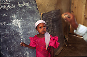 A child in a village school, Ajajia, Ethiopia ready to write on the blackboard.