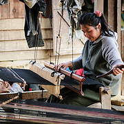 A woman uses her loom in weaving silk fabric in northeastern Laos.