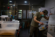 25 March 2020 - 1.5 weeks into coronavirus lockdown. Guillem Giné, the owner of  a small organic bakery Pastisseria Complet in Sant Cugat del Valles, prepares ingredients for tomorrow's bread. Like everywhere in Spain,  the state of emergency and lockdown ensures streets are empty in Sant Cugat del Valles, a normally bustling city of some 90,000 people just outside Barcelona. Most businesses, except those supplying food & pharmacies, are closed. But even if things are quiet, small businesses like Guillem's are toiling away to feed people. By 25th of March Spain had suffered more fatalities from Covid-19 than China, making it the 2nd worst affected country after Italy.  Copyright Dave Walsh 2020.