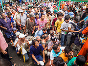"""07 AUGUST 2014 - BANGKOK, THAILAND:     People wait to get into a food distribution at Pek Leng Keng Mangkorn Khiew Shrine in Bangkok. Thousands of people lined up for food distribution at the Pek Leng Keng Mangkorn Khiew Shrine in the Khlong Toei section of Bangkok Thursday. Khlong Toei is one of the poorest sections of Bangkok. The seventh month of the Chinese Lunar calendar is called """"Ghost Month"""" during which ghosts and spirits, including those of the deceased ancestors, come out from the lower realm. It is common for Chinese people to make merit during the month by burning """"hell money"""" and presenting food to the ghosts. At Chinese temples in Thailand, it is also customary to give food to the poorer people in the community.  PHOTO BY JACK KURTZ"""
