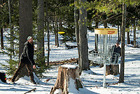 Scott Jarvis makes his putt with at the 7th tee with Eric Benevides Friday afternoon at the Chris Daigle Memorial Disc Golf course at Bolduc Park.  (Karen Bobotas Photo/for The Laconia Daily Sun)