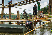 16 SEPTEMBER 2014 - SANGKHLA BURI, KANCHANABURI, THAILAND: Members of the Mon community and Thai soldiers work on the bamboo scaffolding at water level for the repair of the Mon Bridge. The 2800 foot long (850 meters) Saphan Mon (Mon Bridge) spans the Song Kalia River. It is reportedly second longest wooden bridge in the world. The bridge was severely damaged during heavy rainfall in July 2013 when its 230 foot middle section  (70 meters) collapsed during flooding. Officially known as Uttamanusorn Bridge, the bridge has been used by people in Sangkhla Buri (also known as Sangkhlaburi) for 20 years. The bridge was was conceived by Luang Pho Uttama, the late abbot of of Wat Wang Wiwekaram, and was built by hand by Mon refugees from Myanmar (then Burma). The wooden bridge is one of the leading tourist attractions in Kanchanaburi province. The loss of the bridge has hurt the economy of the Mon community opposite Sangkhla Buri. The repair has taken far longer than expected. Thai Prime Minister General Prayuth Chan-ocha ordered an engineer unit of the Royal Thai Army to help the local Mon population repair the bridge. Local people said they hope the bridge is repaired by the end November, which is when the tourist season starts.    PHOTO BY JACK KURTZ