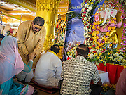 """09 SEPTEMBER 2013 - BANGKOK, THAILAND: A Hindu priest officiates at Ganesha Chaturthi services at the Shiva Temple in Bangkok. Ganesha Chaturthi also known as Vinayaka Chaturthi, is the Hindu festival celebrated on the day of the re-birth of Lord Ganesha, the son of Shiva and Parvati. The festival, also known as Ganeshotsav (""""Festival of Ganesha"""") is observed in the Hindu calendar month of Bhaadrapada. The date usually falls between 19 August and 20 September. The festival lasts for 10 days, ending on Anant Chaturdashi. Ganesha is a widely worshipped Hindu deity and is revered by many Thai Buddhists. Ganesha is widely revered as the remover of obstacles, the patron of arts and sciences and the deva of intellect and wisdom.     PHOTO BY JACK KURTZ"""