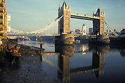 A city landscape showing looking westwards towards Tower Bridge and the river Thames at low-tide with the background of the City of London, the capitals financial district, on 22nd November 1991, in London, England.