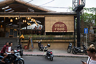Bali, Indonesia - September 19, 2017: Street scene in Ubud, Bali, with motorbikes, a woman walking while looking at her smartphone, and a vacationing couple from Poland eating in a restaurant.