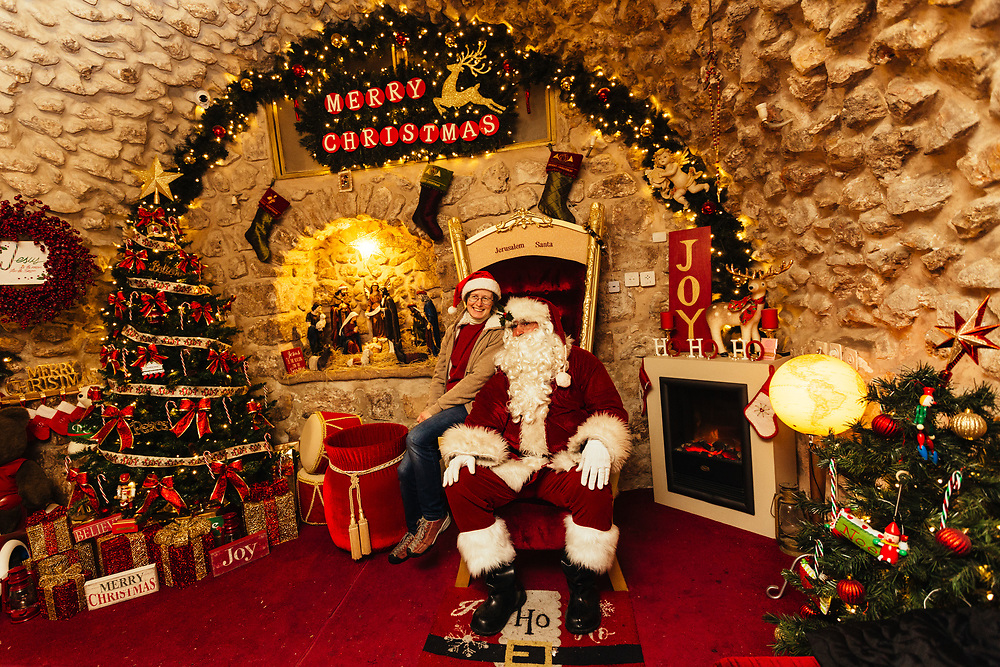A woman sits on Santa's lap, played by Issa Kassissieh, at Santa's House in the Old City of Jerusalem, Israel, on December 19, 2018, before it opens for visitors. Issa Kassissieh, a Christian Arab living in the Old City's Christian Quarter is thought to be Jerusalem's only Santa Claus. He has turned the first floor of his 700-year-old house into Santa's House. He has been doing it for a number of years unofficially, and in July was fully ordained as Santa Claus at a conference in Copenhagen and has even been to Santa school in Denver and Michigan. According to him, he is the only one in Israel and perhaps even in the middle east.