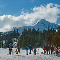 Skiers stand at the base of Big Sky ski area, below Lone Mountain in Big Sky, Montana.