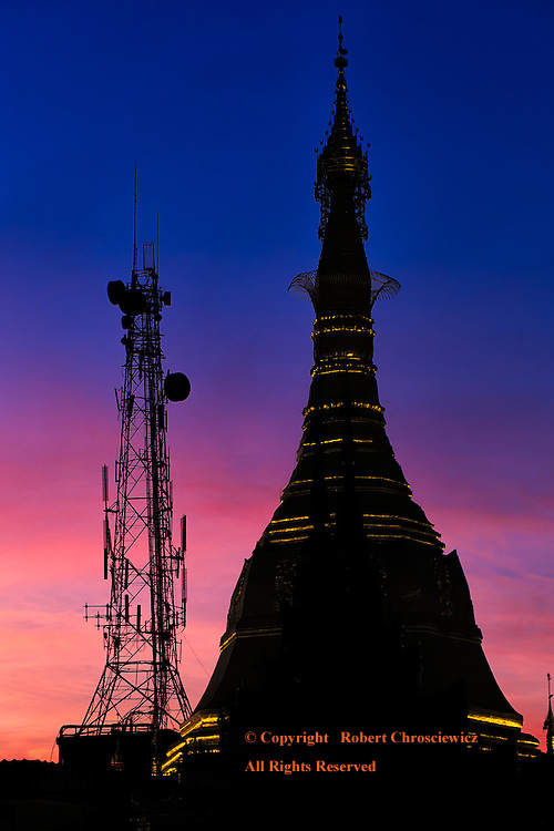 Silhouettes in Contrast: The silhouette of Sule Pagoda stands in stark contrast to the adjacent telecommunication tower, at sunset in downtown Yangon,Myanmar.