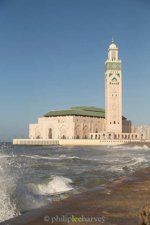 Rough sea with Hassan II Mosque in the background on bright sunny day, Casablanca, Morocco