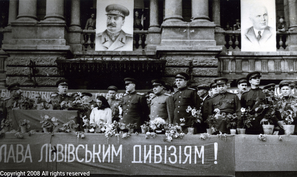 """General Nikita Khrushchev and Generals in Lvov, Ukraine during World War II with portrait of Stalin hanging from building.  From wikipedia, """"In the months following the German invasion, in 1941, Khrushchev, as a local party leader, coordinated the defense of Ukraine but was dismissed and recalled to Moscow after surrendering Kiev."""""""