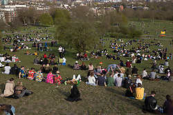 © Licensed to London News Pictures.  17/04/2021. London, UK. Members of the public making the most of the sunny weather in Primrose Hill, north London. Earlier this week Lockdown restrictions were eased to allow non essential retail and outdoor dining to reopen. Photo credit: Marcin Nowak/LNP