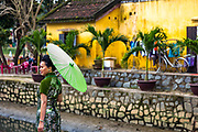 A Vietnamese lady shades the sun with her umbrella in the old city,  with a cafe out of focus behind her.