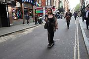 Woman on a skateboard skates along Brewer Street in Soho, London, United Kingdom.