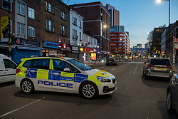 © Licensed to London News Pictures. 23/04/2021. London, UK. A police vehicle at a cordon on Barking Road in Canning Town following the fatal stabbing of a 14-year-old boy. Police were called at 15:56 BST on Friday, 23 April to reports of an assault in Barking Road, E16. Metropolitan Police officers attended with medics from the London Ambulance Service and the London Air Ambulance. They found a 14-year-old male who had been stabbed. He was pronounced dead shortly after 16:30 BST. Photo credit: Peter Manning/LNP