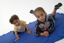 Portrait of brother and baby sister on a rug,