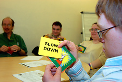 Young man with Downs Syndrome at a learning disabilities support group meeting; uses flash cards to express himself to help communication UK