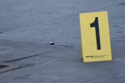 © Licensed to London News Pictures. 21/08/2018. LONDON, UK. An evidence marker is positioned next to a bullet casing at the scene. A police cordon is set up on Imperial Drive near Rayners Lane tube station, north west London, following a shooting in which two men suffered gunshot wounds.  It is reported that the suspect and accomplice have been.   Investigations are ongoing.  Photo credit: Stephen Chung/LNP