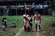DAYAK LONGHOUSE, MALAYSIA. Sarawak, Borneo, South East Asia. Dayak, 'Kelabit', family with longhouse. Tropical rainforest and one of the world's richest, oldest eco-systems, flora and fauna, under threat from development, logging and deforestation. Home to indigenous Dayak native tribal peoples, farming by slash and burn cultivation, fishing and hunting wild boar. Home to the Penan, traditional nomadic hunter-gatherers, of whom only one thousand survive, eating roots, and hunting wild animals with blowpipes. Animists, Christians, they still practice traditional medicine from herbs and plants. Native people have mounted protests and blockades against logging concessions, many have been arrested and imprisoned.