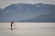 Person paddleboarding on the calm waters near Baldwin Beach along Lake Tahoe, South Lake Tahoe, California