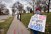 """20 NOVEMBER 2020 - DES MOINES, IOWA: People in front of the Iowa Governor's Mansion protest Iowa's coronavirus response. About 20 people participated in a protest in front of the Iowa Governor's Mansion Friday. They called on Governor Kim Reynolds to immediately issue a comprehensive mask mandate across Iowa. Reynolds, a Republican, has ordered a partial mask mandate that excuses some congregate settings, like classrooms. Iowa has one of the highest per capita COVID-19 infection rates in the country and is dealing with wide """"community spread"""" of the Coronavirus (SARS-CoV-2) throughout the state.      PHOTO BY JACK KURTZ"""
