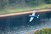 An RAF spitfire fighter plane flies over Ladybower Reservoir in the Upper Derwent Valley as part of the Dambusters 617 Squadron 70th Anniversary Commemorative Flypast. May 16th 2013. Derbyshire, Peak District.