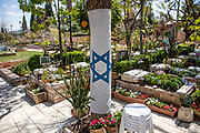 The Israeli national flag tied to a tree at Kiriyat Schaul Military Cemetery, Ramat Ha Sharon, Israel April 13, 2021.  Israel will commemorate this year's Memorial  in remembrance of it's soldiers who fell in the line of duty and of  and civilians who where killed in acts of terror. Services and ceremonies were cancelled during 2020 due to the coronavirus pandemic, this year, as vast percentage of the population are vaccinated, ceremonies will be able to take place in a some what ordinary manner.