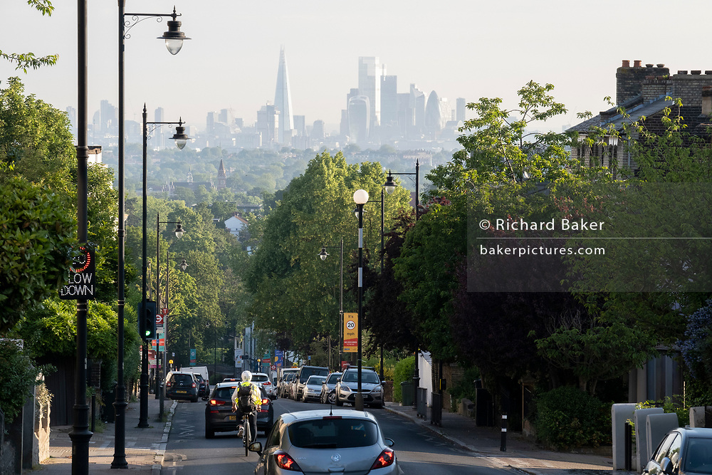 With the London skyline in the far distance, a cyclist and traffic descend 20mph steep gradient of Gypsy Hill in Crystal Palace, on 16th June 2021, in London, England.