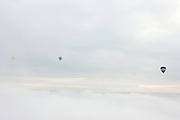 Drie heteluchtballonnen varen boven de wolken<br /> <br /> Three air ballons in the sky above the clouds.