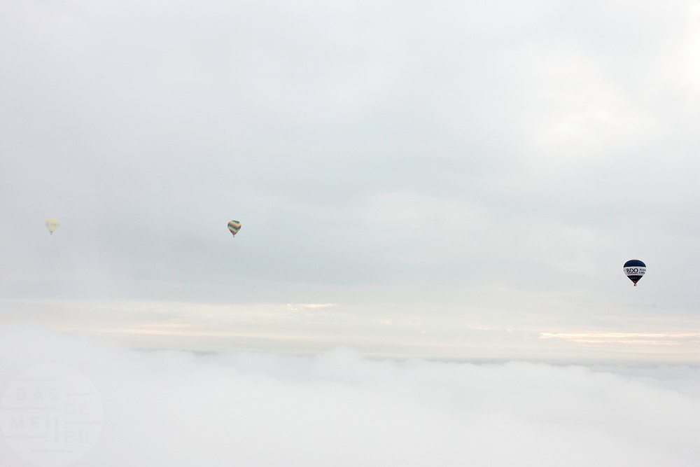 Drie heteluchtballonnen varen boven de wolken<br /> <br /> Three air ballons in the sky above the clouds.