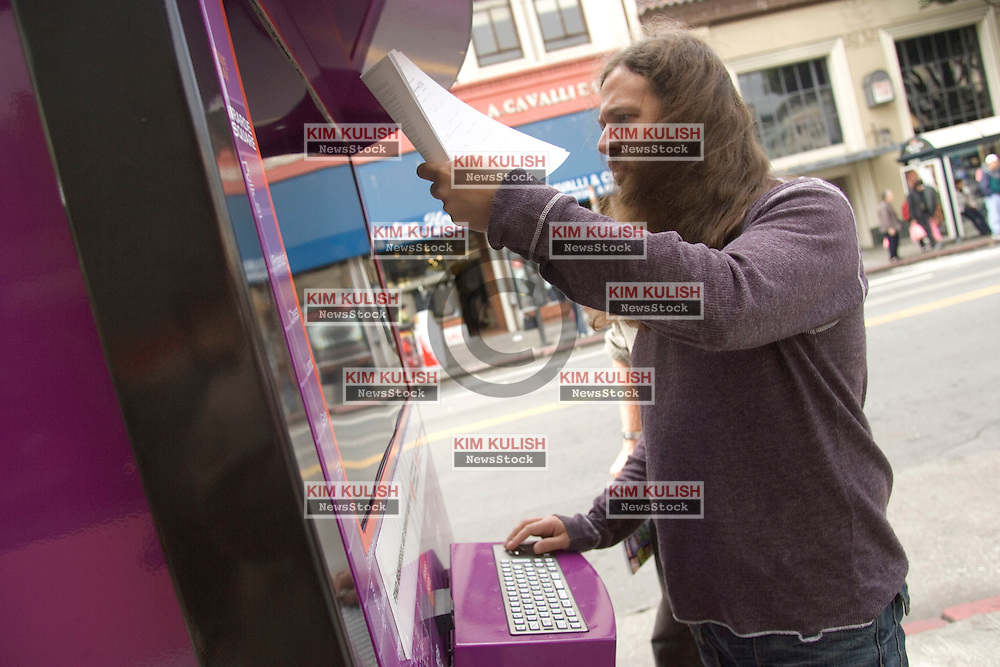 People look for information at the Yahoo interactive bus stop in the North Beach section of San Francisco, Calif. Yahoo has launched the world's first  internet enabled bus stop in San Francisco, and  plans others in New York and Los Angeles to promote their new search offering, Yahoo!, Local. The bus stops feature an internet connected 42 inch plasma monitor, keyboard, and printer so users can print information and maps on site. Photo ©2004  by Kim Kulish