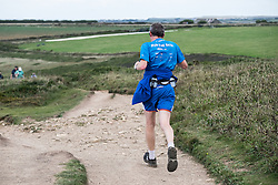 A runner on the South West Coastal path at Carnewas at Bedruthan in Cornwall.
