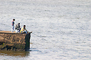 three Men sitting on a pier fishing, one holding a fishing pole. Looking cold., on the riverside seaside walk along the river Rio de la Plata Ramblas Sur, Gran Bretagna and Republica Argentina Montevideo, Uruguay, South America