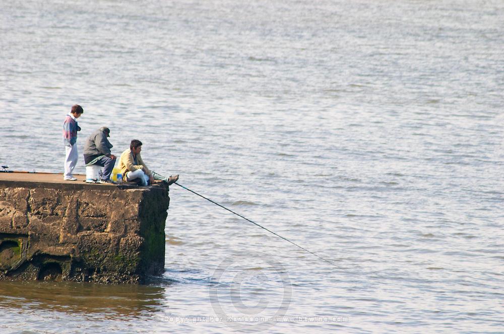 three Men sitting on a pier fishing, one holding a fishing pole. Looking cold., on the riverside seaside walk along the river Rio de la Plata Ramblas Sur, Gran Bretagna and Republica Argentina Montevideo, Uruguay, South America
