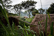 A woman sets fire to her garden in an empty refugee camp for Central Republic of Africans fleeing LRA attacks in Source Yobu South Sudan. The refugees were moved to a larger Congolese camp in a more secure area, some families choose to remain behind.