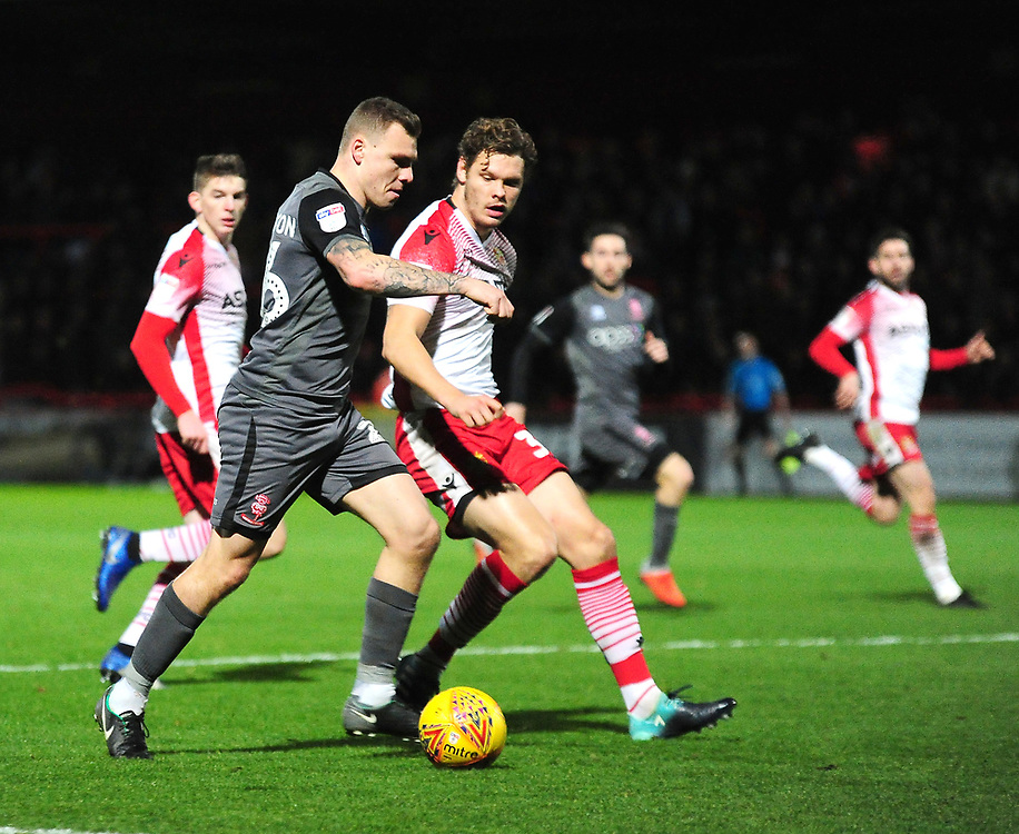 Lincoln City's Harry Anderson crosses under pressure from Stevenage's Ben Nugent<br /> <br /> Photographer Andrew Vaughan/CameraSport<br /> <br /> The EFL Sky Bet League Two - Stevenage v Lincoln City - Saturday 8th December 2018 - The Lamex Stadium - Stevenage<br /> <br /> World Copyright © 2018 CameraSport. All rights reserved. 43 Linden Ave. Countesthorpe. Leicester. England. LE8 5PG - Tel: +44 (0) 116 277 4147 - admin@camerasport.com - www.camerasport.com