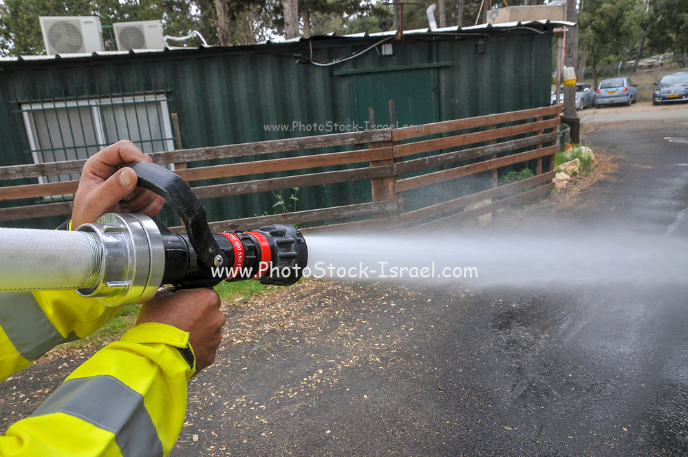 Fireman in protective clothing extinguishes a fire as part of a fire fighting drill