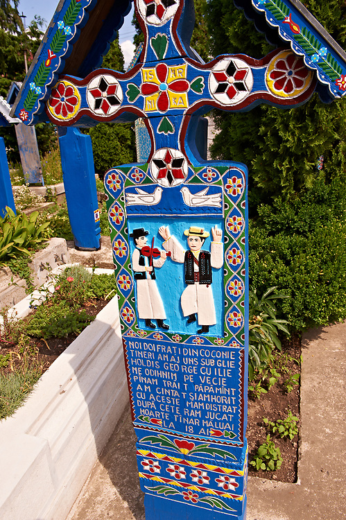 Tombstone showing a man doing a traditional dance,  The  Merry Cemetery ( Cimitirul Vesel ),  Săpânţa, Maramares, Northern Transylvania, Romania.  The naive folk art style of the tombstones created by woodcarver  Stan Ioan Pătraş (1909 - 1977) who created in his lifetime over 700 colourfully painted wooden tombstones with small relief portrait carvings of the deceased or with scenes depicting them at work or play or surprisingly showing the violent accident that killed them. Each tombstone has an inscription about the person, sometimes a light hearted  limerick in Romanian. .<br /> <br /> Visit our ROMANIA HISTORIC PLACXES PHOTO COLLECTIONS for more photos to download or buy as wall art prints https://funkystock.photoshelter.com/gallery-collection/Pictures-Images-of-Romania-Photos-of-Romanian-Historic-Landmark-Sites/C00001TITiQwAdS8