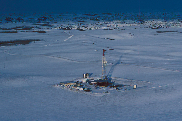 Stock photo of an aerial view of a snow covered oil and gas drilling rig site in Wyoming