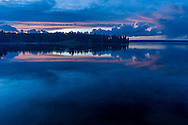 Pink clouds reflected in Yellowstone Lake during sunset after a recent summer thunderstorm. Yellowstone National Park, Wyoming.