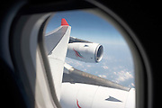 Clouds and blue sky above the Indian Ocean are far below a Sri Lankan Airbus aircraft port wing and CFM engines.