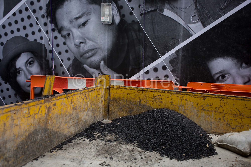 The faces on a construction site hoarding peer over a contractor's pile of tarmac in the back of a small truck, on the corner of Limeburner Lane and Ludgate Hill, EC4. A man appears to be looking at the small pile of tarmac with a doubtful expression and others look towards the viewer. The construction and development company Skanska is responsible for its design, maintaining a clean and tidy site, separating the dangers of the site and Londoners at street level.