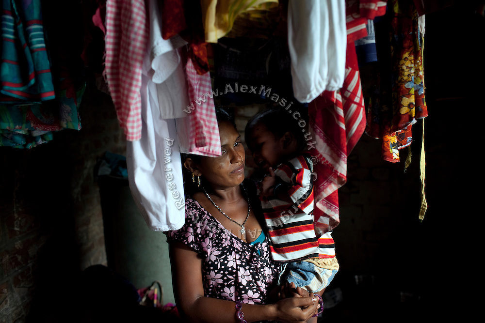 The older sister of Neelam Bharadwaj, 16, (name changed) Sanju, 29, is carrying her youngest son, Prince Kumar, 3, while inside her family's home in Rajbhar village, located around 20 kilometres away from Varanasi, in Uttar Pradesh, India. Neelam was raped when she was 13 years old. After walking to a local shop on the main road neighbouring her village, she was forcibly picked up by two men. While one of them was raping her in the bushes, the other watched out. After some time, she managed to free herself and run away, hiding under a bridge in cold dirty water for several hours. When she returned home in the morning, the family was too afraid to go to the police, but activist Mangla Parsad, 34, from PVCHR, convinced the family to take the right action. The police initially insulted and threatened the family for bringing the facts up, but filed the official case (FIR) nevertheless. The rape was not mentioned in the file due to an inaccurate and superficial medical record that did not, in fact, mention it. Because of social shame facing by victims of rape in India, the family agreed to wed Neelam to an older man, with help of an agent. After the marriage, her husband raped her again for a whole month before she decided to return home with her family. Neelam's father works in the metal industry in Mumbai and manages to send around 2-3000 INR every month. He only visits the family once in a year. Neelam goes to school and she is studying in 11th Class Standard. She is interested in doing BA in Arts after completing her high school 12th final year.