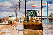 24 JANUARY 2010 -- WENDEN, AZ:  A loader in Wenden scrapes mud off the street. Wenden was slammed by its second 100 year flood in 10 years on Thursday night when water raced through Centennial Wash and into the small town in La Paz County west of Phoenix. Most of the town's residents were evacuated to Red Cross shelters in Salome, about 5 miles west of Wenden.    PHOTO BY JACK KURTZ