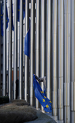 A worker raises the EU flags at the European Commission headquarters, in Brussels, Belgium, on Monday, Dec. 19, 2011. (Photo © Jock Fistick).